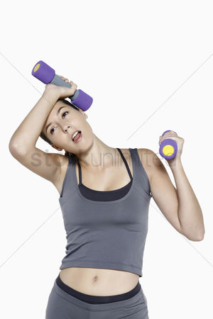 Dumbbell : Woman looking exhausted after working out with dumbbells