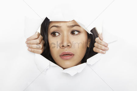 Young woman : Woman looking through a torn paper