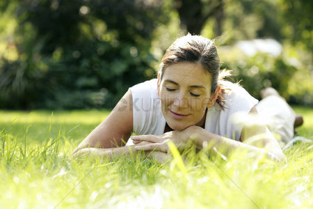 Relaxing : Woman lying forward on the field with her eyes closed