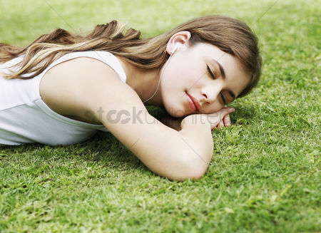 Comfort : Woman lying forward on the grass listening to music