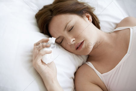 Cold : Woman lying in bed with cold close up