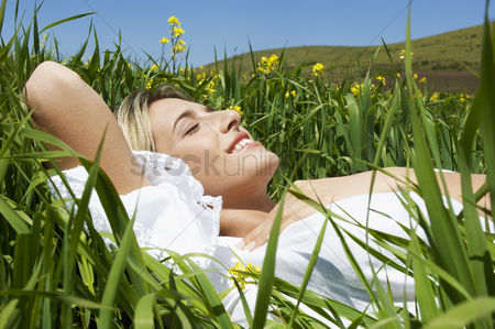 Young woman : Woman lying in mountain meadow close up