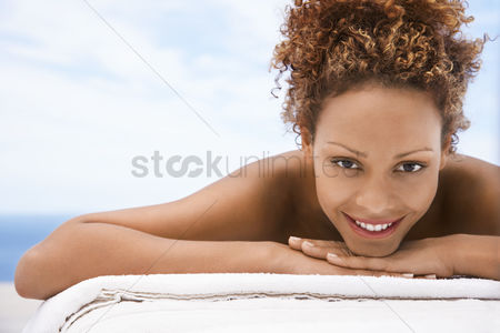 Curly hair : Woman lying on massage table head and shoulders eye contact