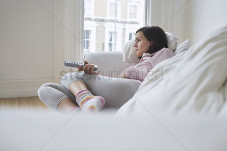Pink : Woman lying on sofa watching television