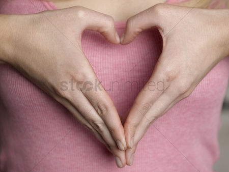 Finger : Woman making heart shape with hands close-up mid section