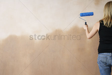 Denim : Woman painting wall with paint roller back view