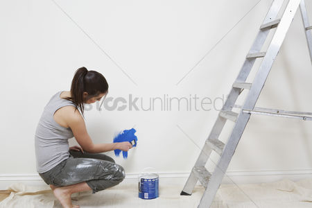 Paint brush : Woman painting wall