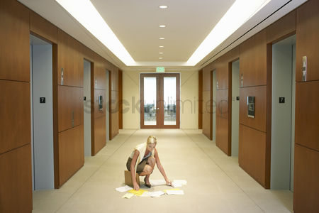 Choosing : Woman picking dropped papers from floor in elevator lobby elevated view