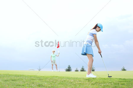 Flag : Woman playing golf with female friend against sky