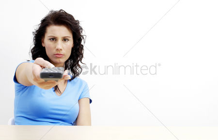 Composed : Woman pointing a remote control at the camera