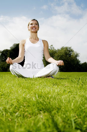 Resting : Woman practicing yoga in the park