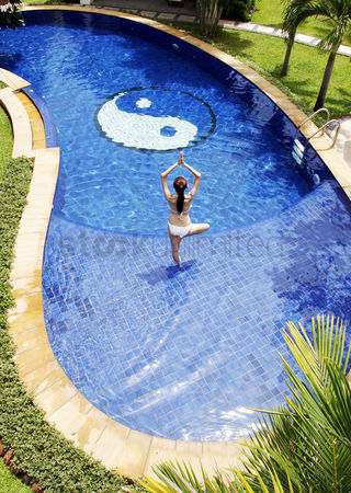 Outdoor : Woman practising yoga in the swimming pool