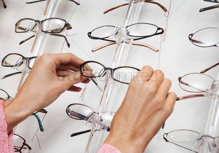 Choosing : Woman pulling glasses from display rack close up of hands
