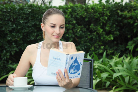 Food  beverage : Woman reading book while enjoying a cup of tea outdoors