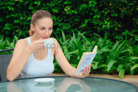 Eastern european ethnicity : Woman reading book while enjoying a cup of tea outdoors