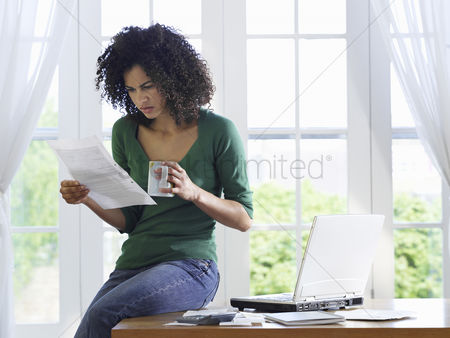 Window : Woman reading paper document sitting on desk