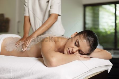Indulgence : Woman receiving back massage with coconut scrub