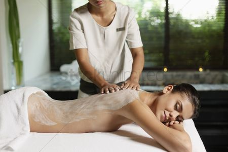 Relaxing : Woman receiving back massage with coconut scrub