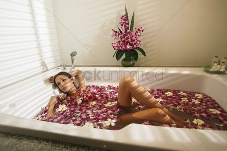 Arm raised : Woman relaxing in bathtub with flower petals