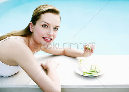 Lying forward : Woman resting by the pool side eating green vegetables