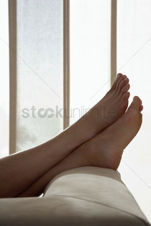 Modern lifestyle : Woman resting with feet up on sofa in living room close up of feet low section