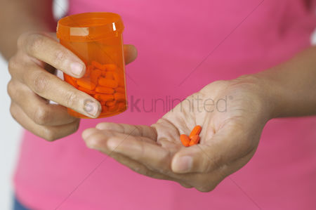 Medication : Woman s hands holding pills and bottle close-up
