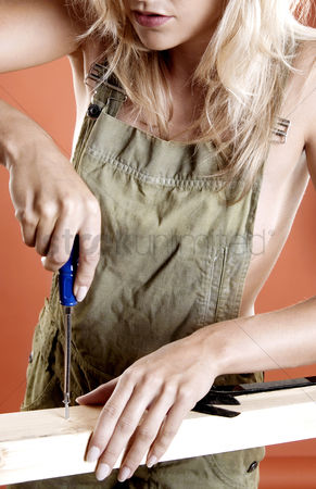 Fixing : Woman screwing screw into a wood