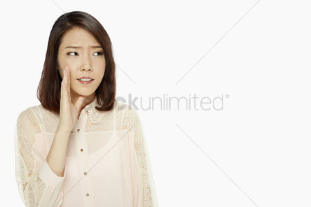 Frowning : Woman showing a whispering hand gesture