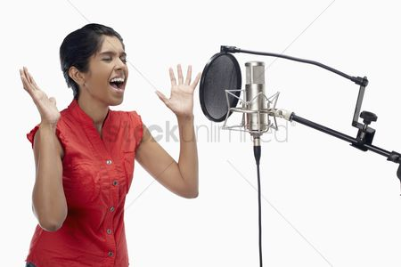 Arts : Woman singing in recording studio