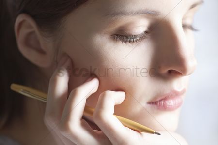 Ponytail : Woman sits holding pencil and leaning on chin