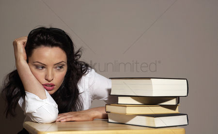 Thought : Woman sitting at her desk looking at a stack of thick books