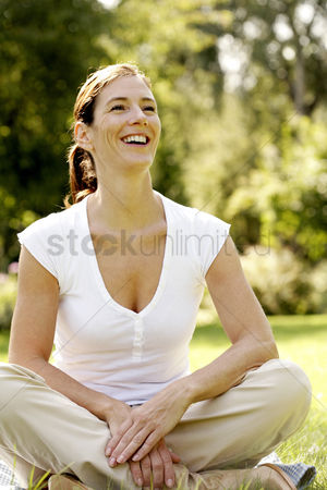 Grass : Woman sitting in a park smiling