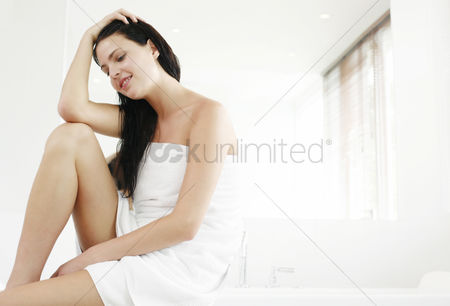 Satisfying : Woman sitting on bathtub ledge thinking