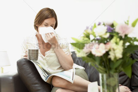 Blowing : Woman sitting on sofa blowing nose