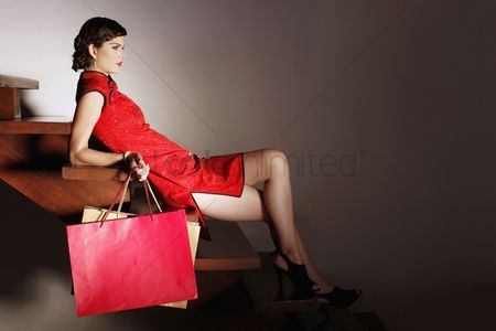 Fashion : Woman sitting on stairs carrying shopping bags