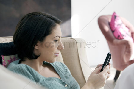Cellular phone : Woman sitting on the couch text messaging on the phone
