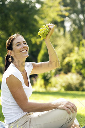 Green grapes : Woman sitting on the field holding green grapes
