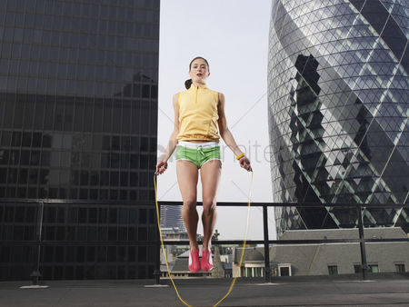 Fitness : Woman skipping on skipping rope on downtown rooftop low angle view london england