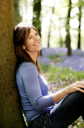 Rest : Woman smiling while leaning against a tree