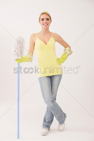 Housewife : Woman standing and holding mop
