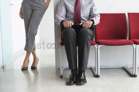 Pocket : Woman standing beside man on chairs in corridor