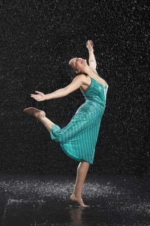 Celebrating : Woman standing on one leg leaning into falling rain
