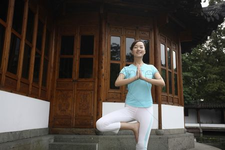 Practising yoga : Woman standing on one leg