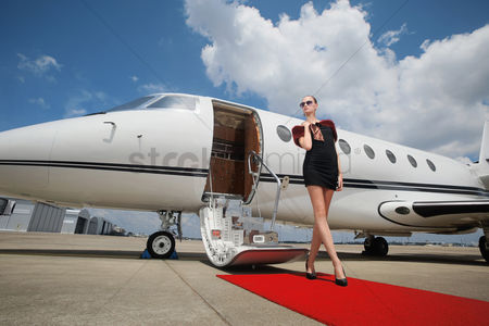 Fashion : Woman standing on red carpet upon exiting private jet