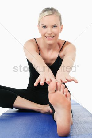 British ethnicity : Woman stretching on yoga mat