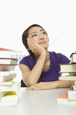 Daydream : Woman surrounded by books  looking bored