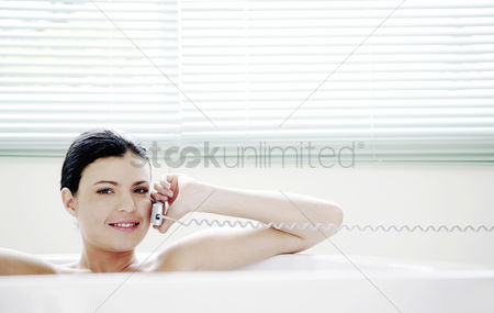 Satisfying : Woman talking on the phone while sitting in the bathtub