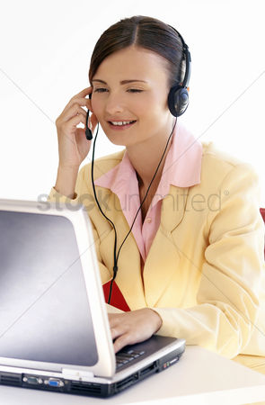 Answering calls : Woman talking on the telephone headset while using the laptop