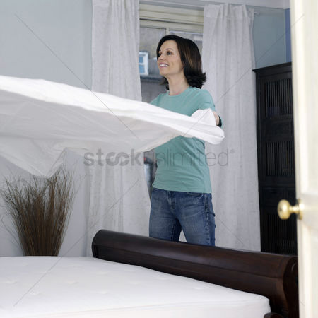 Housewife : Woman throwing blanket on the mattress