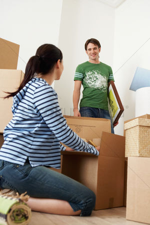 First : Woman unpacking box man looking